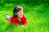 image of 7-year-old  - 7 years old boy lying on a grass and listening to music in headphones - JPG