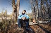 stock photo of ukulele  - Man in blue shirt with bow tie and ukulele on the tree trunk in the forest - JPG
