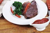 picture of kale  - grilled beef steak fillet meat with red hot pepper and  raw kale leaf with ketchup sauce served on white plate over wood table - JPG