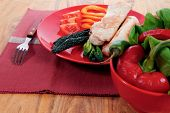 picture of kale  - fresh roast turkey meat fillet steak on red plate with tomatoes pepper green kale and lettuce salad over wooden table - JPG
