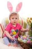 picture of baby easter  - Beauty baby with pink bunny ears holding easter eggs and sitting on fluffy blanket - JPG