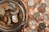 foto of copper coins  - A collection of coins in a glass jar surrounded by coins - JPG