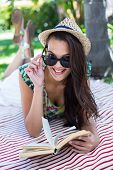 picture of palm-reading  - Smiling beautiful brunette lying and reading a book with palm tree behind her - JPG