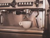 pic of dispenser  - Professional coffee machine with a small white cup ready for coffee being dispensed - JPG
