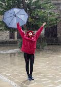 pic of dancing rain  - Young beautiful caucasian woman with an umbrella dressed in Red and dancing in the rain.