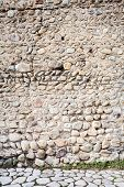 foto of fortified wall  - Ancient wall of stones and a pavement - JPG
