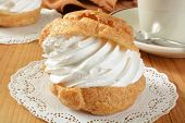stock photo of cream puff  - A large golden cream puff on a doily with a cup of coffee - JPG