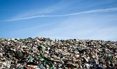 picture of landfills  - Landfill with bulldozer working against beautiful blue sky full of sea birds - JPG