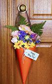 picture of door-handle  - Happy May Day traditional gift of Spring flowers in orange cone hanging from door handle on wooden door - JPG