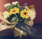 image of gift basket  - Happy Mothers Day gift of Spring Flowers on dark wood table and rustic dark red background with applied retro vintage style filters and added sun lens flare - JPG
