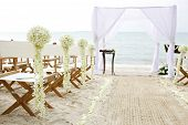 foto of ceremonial clothing  - white cloth wedding tent setup and white canvas folding chairs seating arrangement with white orchid stands  decoration on the beach in sea breeze atmosphere - JPG