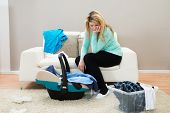 foto of dirty-laundry  - Unhappy Mother With Laundry Clothes And Baby In Cradle - JPG