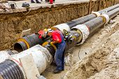 stock photo of pipe-welding  - Metal worker is grinding weld on new pipeline heating system - JPG