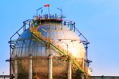 stock photo of petroleum  - natural petrochemical gas storage tank in heavy petroleum industry estate against clear blue sky background - JPG
