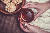 stock photo of crispy rice  - Woman holding cup of black tea on white woollens and rice crispy balls in wooden bowl close up - JPG