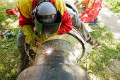stock photo of overalls  - Welder working on a pipeline in construction site wearing overall and safety equipment - JPG
