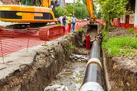 picture of pipeline  - Team of workers in trench working hard to install a new pipeline - JPG