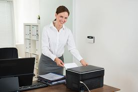 image of secretary  - Young Female Secretary Inserting Paper In Printer At Desk - JPG
