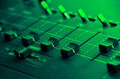 Sound mixer console under green disco light