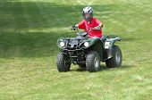 stock photo of four-wheeler  - Young boy riding four - JPG