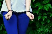 Fragment Of A Young Criminal Girls Body With Hands In Handcuffs Against A Green Blossoming Ivy Leav poster