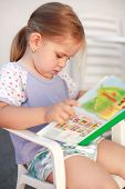 stock photo of storytime  - Small girl is reading a picture book - JPG