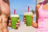 Green smoothie fit fitness healthy people drinking juice at exercise workout. Closeup of couple hand poster
