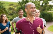 Portrait of a happy cheerful man listening to music while jogging. Man listening to music while jogg poster