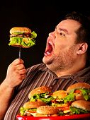 Diet failure of fat man eating fast food . Happy smile overweight person who crazy makes squint for  poster