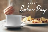 Cup of coffee and breakfast on table. Text HAPPY LABOR DAY on blurred background poster