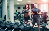 Personal Trainer Helping Woman Working With Heavy Dumbbells. Personal Fitness Instructor. Personal T poster