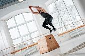 Dynamic Shot Of Fitness Male Athlete Jumping At Square Box In Gym. Strong Man Doing Jump On Wooden S poster