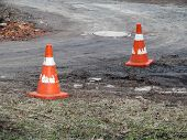 Two Old Shabby Construction Cones Are On A Dirt Road. Orange Traffic Cones With Shabby White Stripes poster