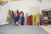 An Older Woman In A Dark Coat Cuts The Marked Grey Material For The Sofa. Behind The Are Different T poster