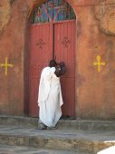 A Christian Coptic priest locking a church carved entirely out of stone in Ethiopia