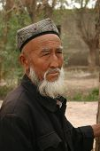 A Uyghur man from Kashgar China looking over cattle at an animal auction