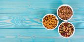 Various Cat Food. Dry And Wet Cat Food. Copy Space. Bowls With Cat Food On Wooden Background. poster