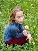 Young girl sitting on grass and blowing a dandellion