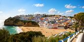 View of the sandy beach surrounded by typical white houses in a sunny spring day, Carvoeiro, Lagoa,  poster