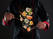 Closeup of master chef holding wooden chopsticks with flying sushi pieces. Concept of food preparati poster