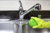 image of cleaning service  - A person cleaning the kitchen sink with a glove - JPG