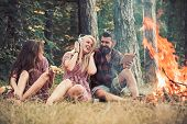 Friends Relax At Bonfire Flame With Sparks In Vintage Style. People Camping At Fire In Forest. Women poster