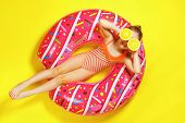 A Little Child Girl In A Swimwear Suit Lying On A Donut Inflatable Circle. Yellow Background. Top Vi poster