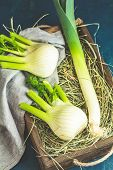 Fresh Florence Fennel Bulbs Or Fennel Bulb, Leek And Parsley In Wooden Box With Dried Grass On Dark  poster