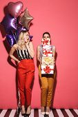 Portrait of two pretty women 20s in stylish outfit holding present boxes and balloons on party isola poster