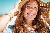 Portrait of beautiful woman wearing straw hat with large brim at beach and looking at camera. Closeu poster