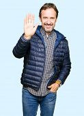 Middle age handsome man wearing winter coat Waiving saying hello happy and smiling, friendly welcome poster