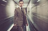 image of escalator  - Man in classic grey suit with briefcase standing on escalator - JPG
