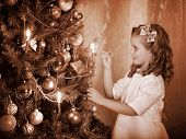 Little girl lights candles on  Christmas tree. Black and white retro.