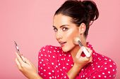 Beautiful young brunette woman applying blusher to her cheek using a cosmetic brush and small compact mirror
